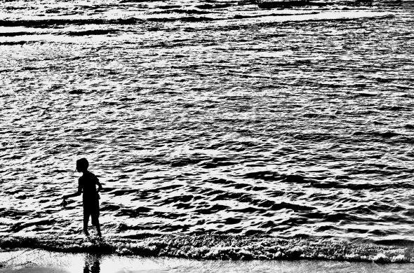 ילד על החוף שחור לבן