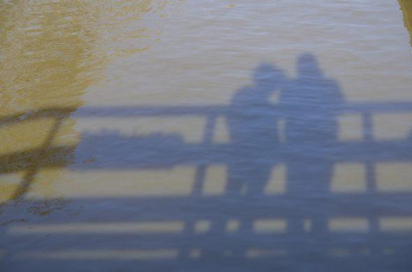 צללית של זוג על המים